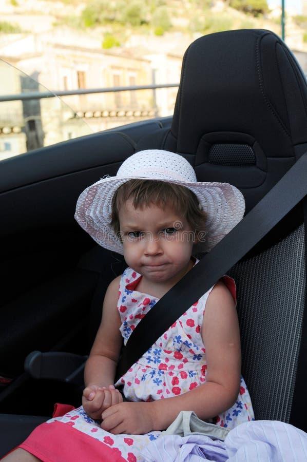 Niña con el cinturón de seguridad   foto de archivo