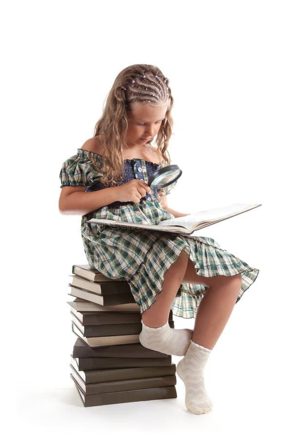 Niña con el libro de lectura de la lupa foto de archivo libre de regalías