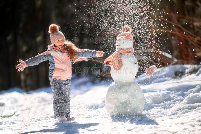 Niña con el muñeco de nieve imagenes de archivo