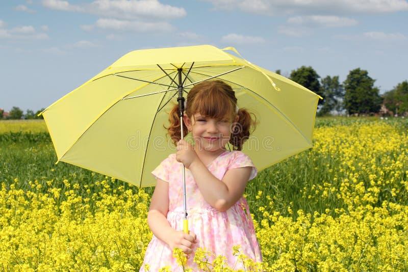 Niña con el paraguas amarillo imagen de archivo