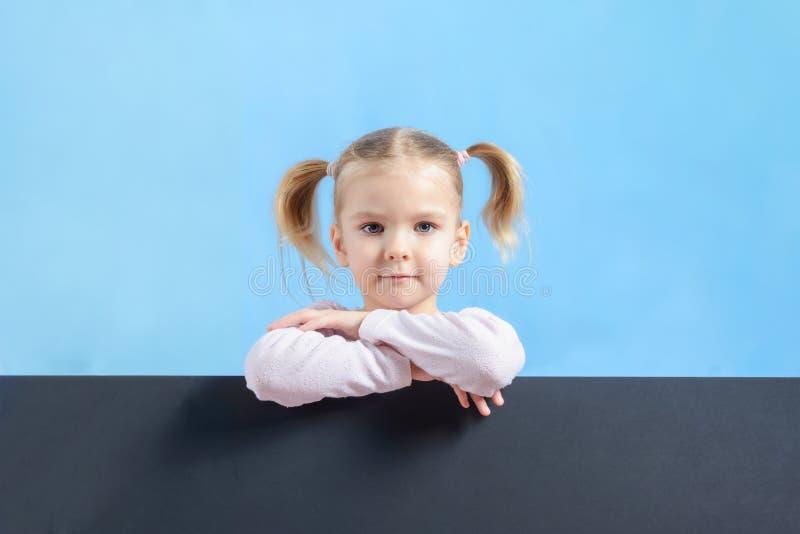 Niña con el pelo rubio en un fondo azul El niño tiene un pelo de dos colas Parte inferior en una hoja negra de la cartulina fotografía de archivo