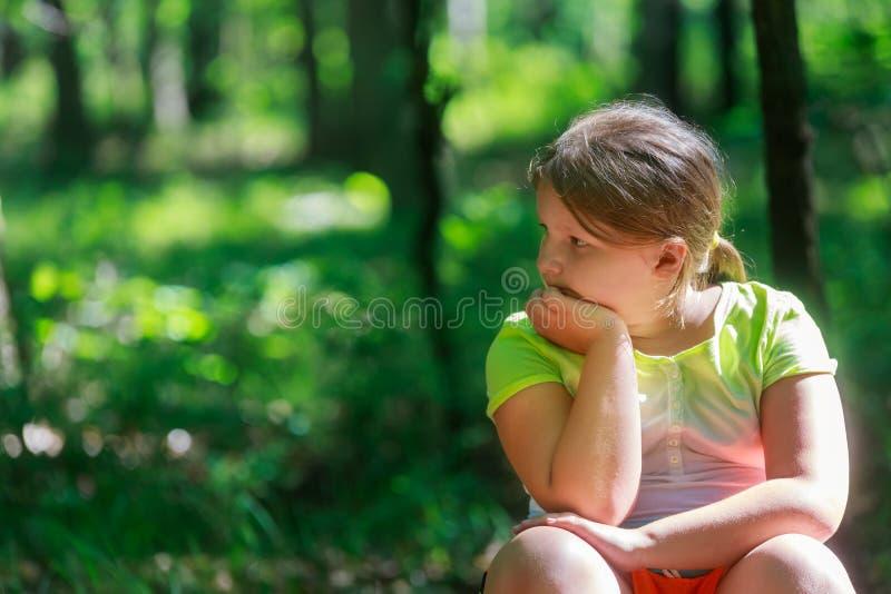 Niña con el pelo rubio que se sienta en parque y miradas del otoño en el lado izquierdo imágenes de archivo libres de regalías