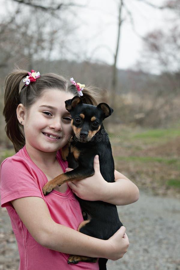 Niña con el perrito foto de archivo