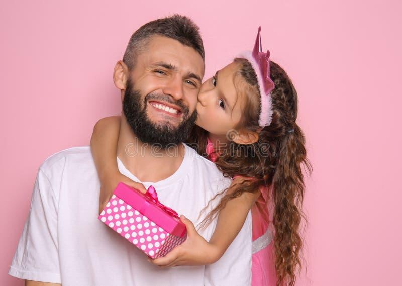 Niña con el presente que besa a su padre en fondo del color foto de archivo libre de regalías