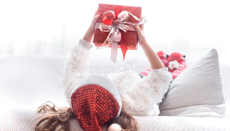 Niña con el regalo de la Navidad en el traje de Papá Noel fotografía de archivo libre de regalías
