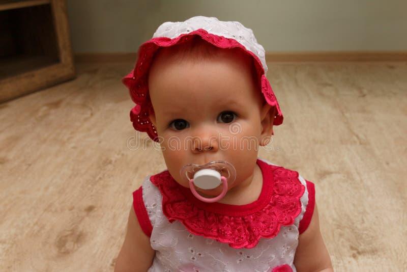 Niña con el soother pequeño bebé con un pacificador en un vestido y un sombrero blancos y rosados, se sienta en el piso y mira el foto de archivo