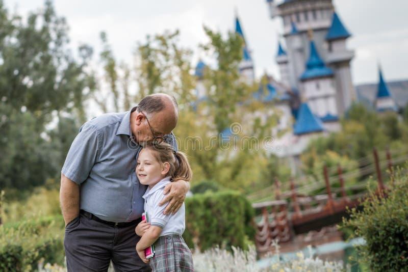 Niña con el uniforme escolar y su abuelo en par verde fotos de archivo