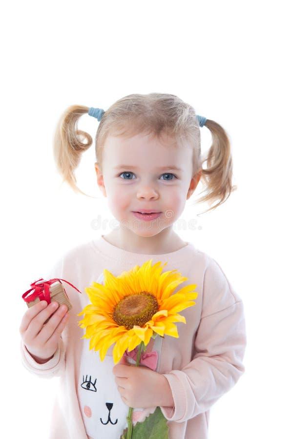 Niña con flores y un regalo imagen de archivo libre de regalías