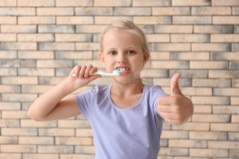 Niña con gesto del pulgar-para arriba de la demostración del cepillo de dientes contra la pared de ladrillo fotos de archivo