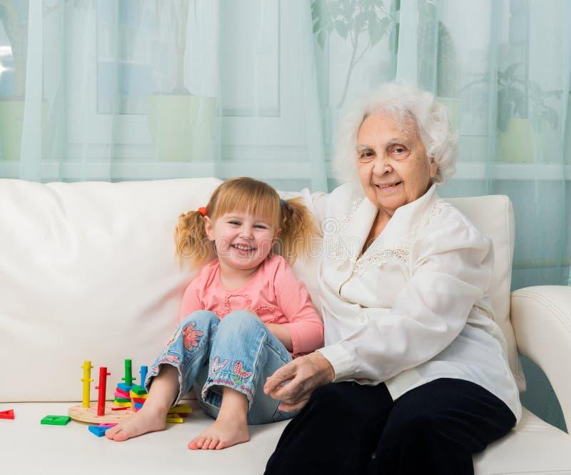 Niña con la abuela en un sofá imágenes de archivo libres de regalías