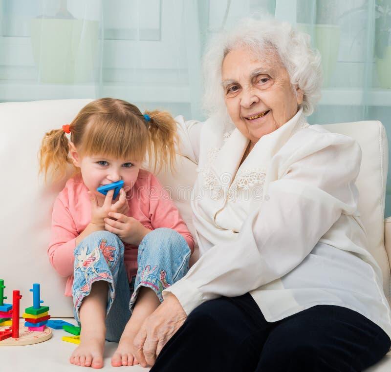 Niña con la abuela en un sofá imagen de archivo libre de regalías