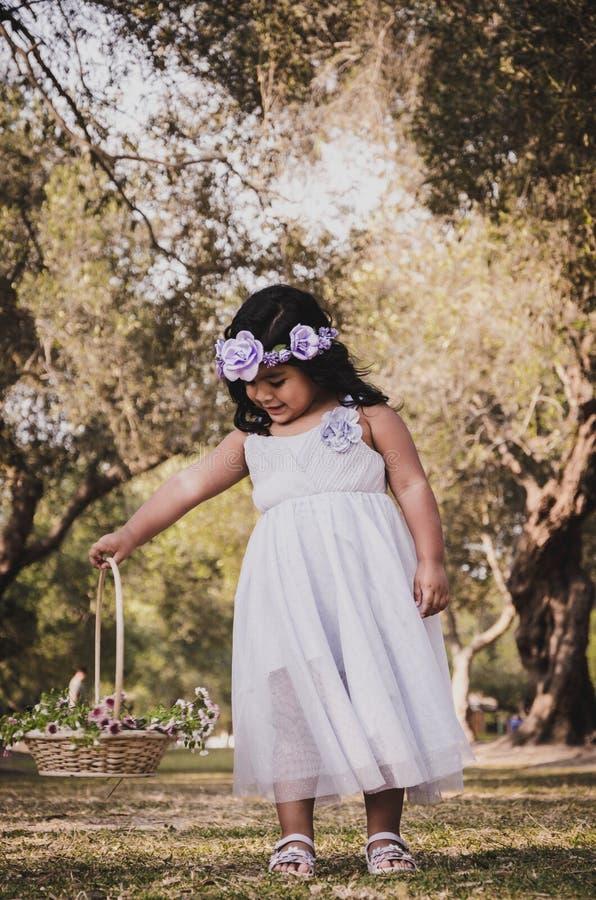 Niña con la cesta de la flor fotos de archivo