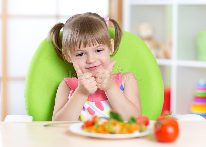 Niña con la comida de las verduras que muestra el pulgar para arriba fotografía de archivo libre de regalías