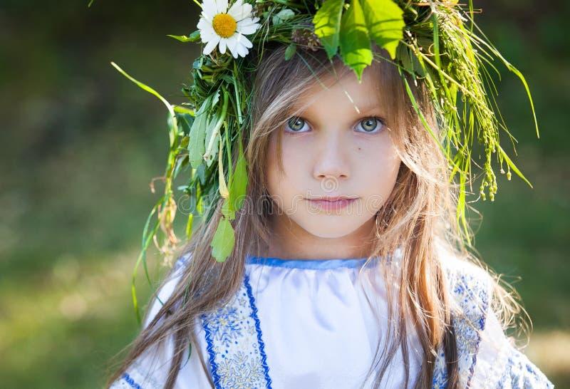 Niña con la guirnalda de la flor imagenes de archivo