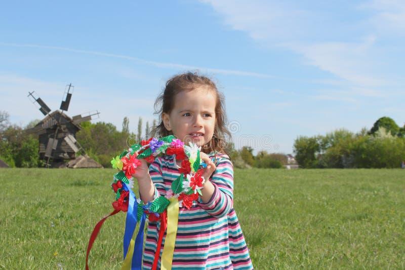 Niña con la guirnalda de la flor en el campo con el molino de viento viejo detrás imagen de archivo libre de regalías