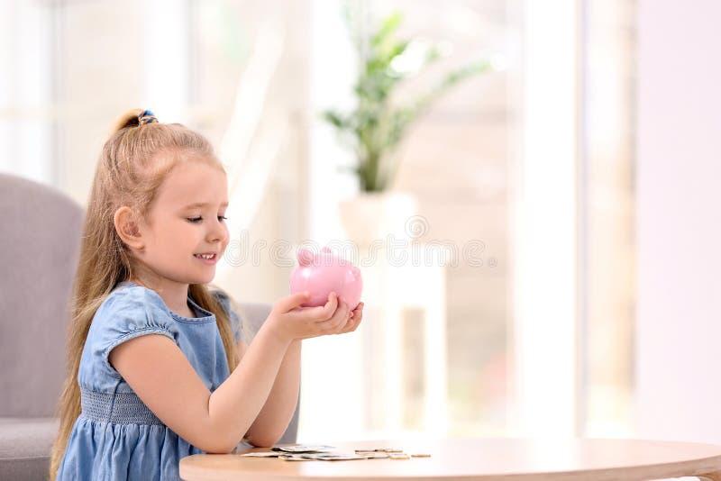 Niña con la hucha y el dinero en casa imágenes de archivo libres de regalías