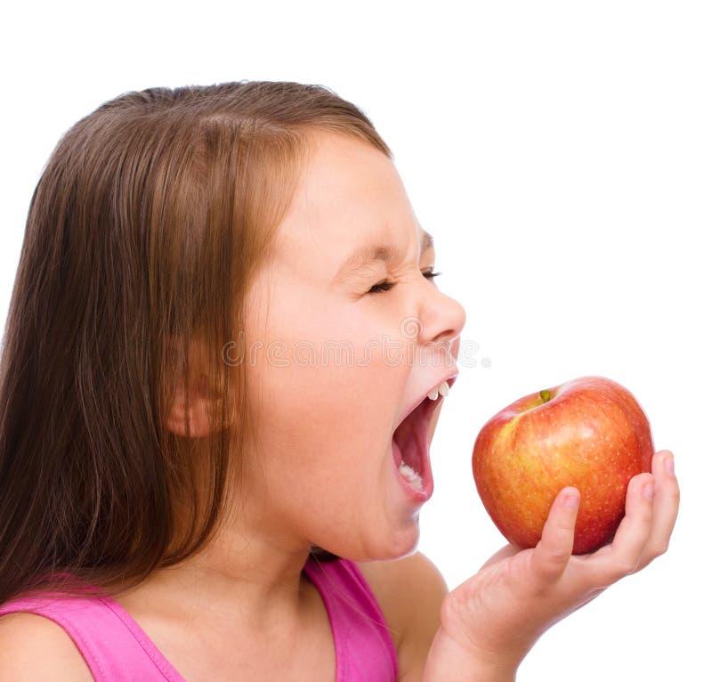 Niña con la manzana roja imagenes de archivo