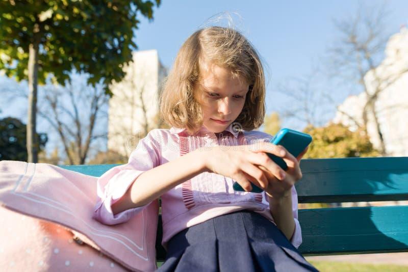 Niña con la mochila y el teléfono móvil que se sientan en banco Niño que usa el smartphone, día soleado en el parque imagenes de archivo