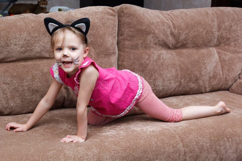 Niña con la pintura de la cara del gato en el sofá imágenes de archivo libres de regalías