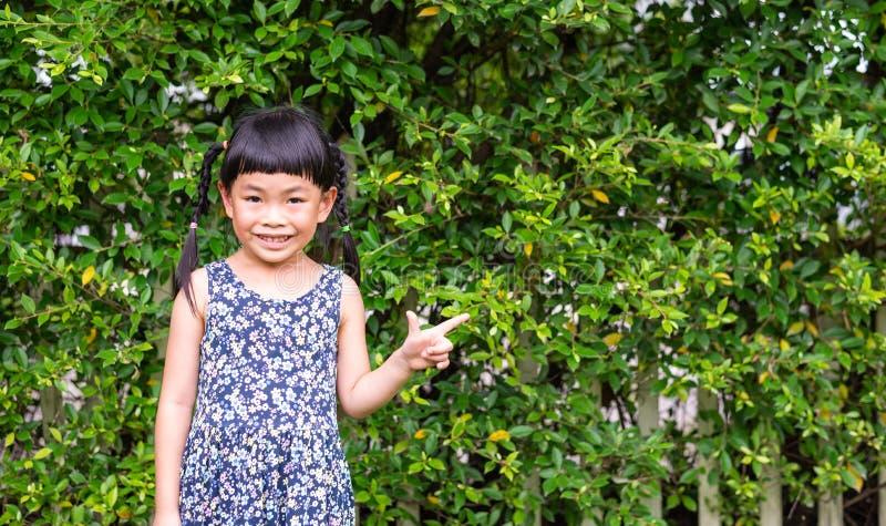 Niña con la sonrisa grande que se coloca delante de la cerca con la planta imagen de archivo