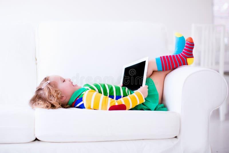 Niña con la tableta en un sofá blanco imagen de archivo