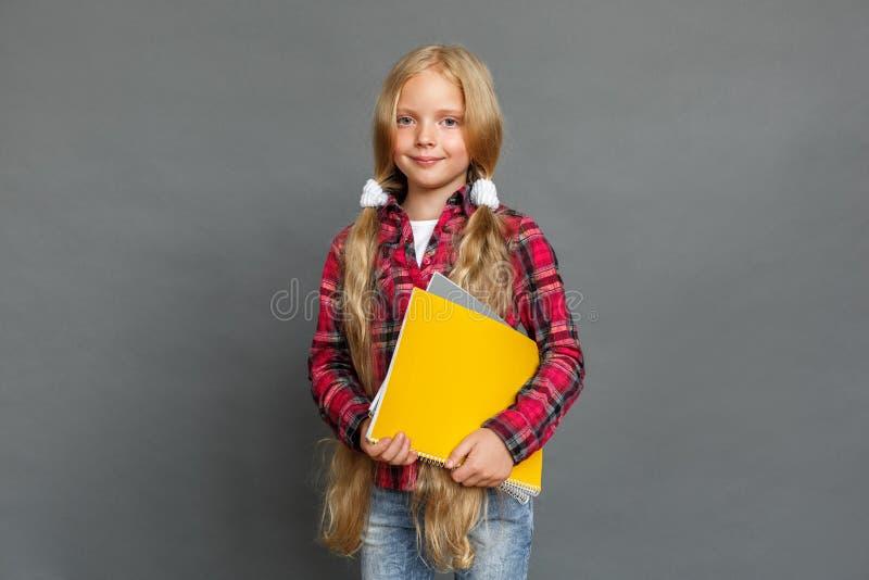 Niña con las colas de caballo que se colocan aislada en gris con los cuadernos que miran la cámara feliz imagen de archivo