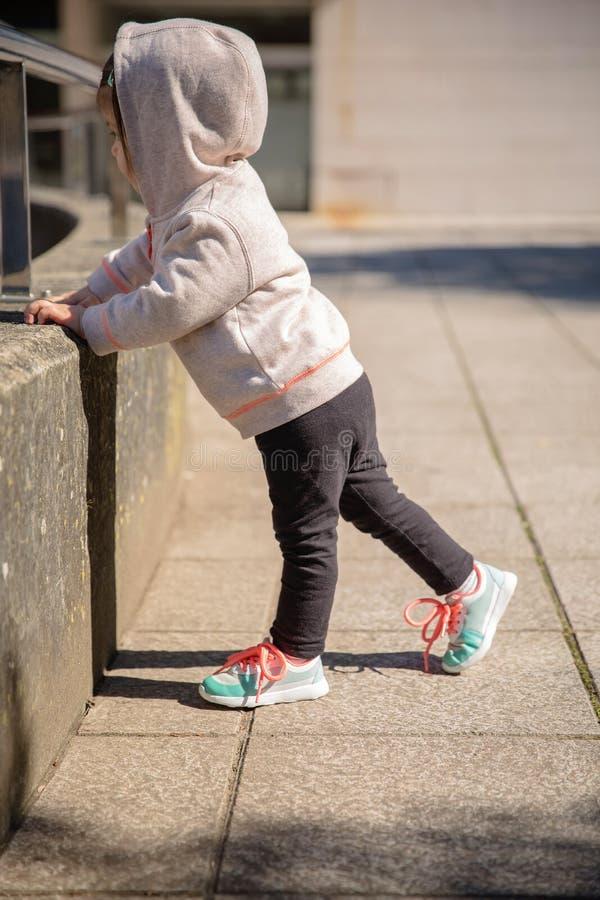 Niña con las zapatillas de deporte y calentarse de la sudadera con capucha imágenes de archivo libres de regalías