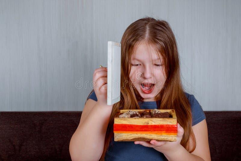 Niña con los caramelos en caja sorprendida sosteniendo un bastón de caramelo Feliz Navidad foto de archivo