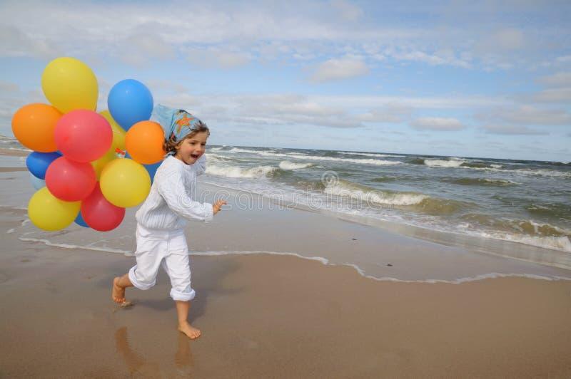Niña con los globos en la playa imagen de archivo