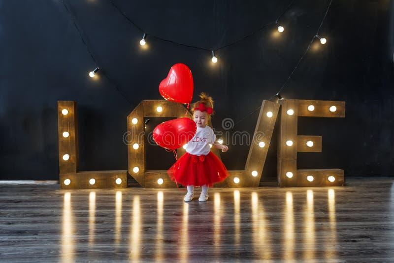Niña con los globos rojos en estudio el día de tarjeta del día de San Valentín del santo foto de archivo libre de regalías