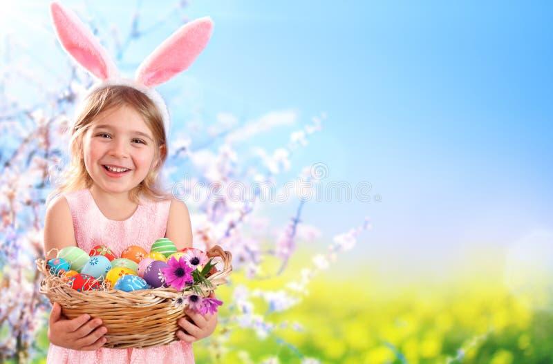 Niña con los huevos y Bunny Ears-Easter de la cesta imagenes de archivo