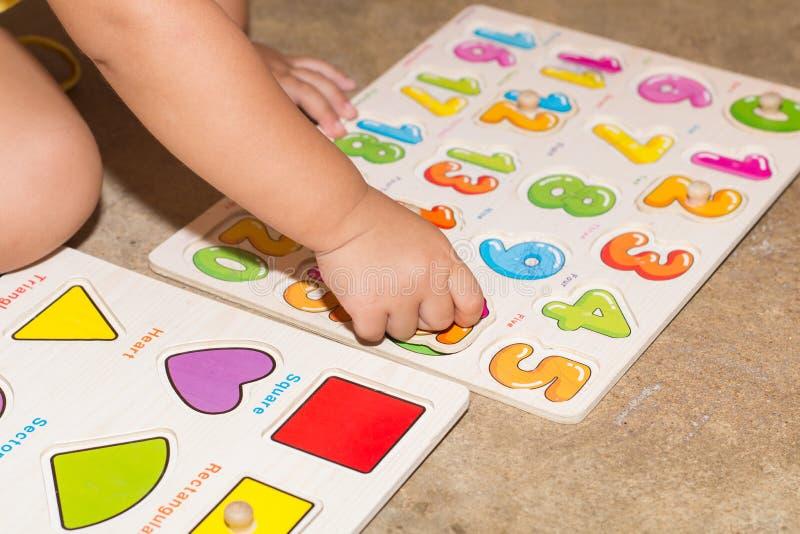 Niña con los juegos educativos de los números del juguete en casa, juegos de mesa para el aprendizaje moderno de los niños, mucha fotografía de archivo libre de regalías