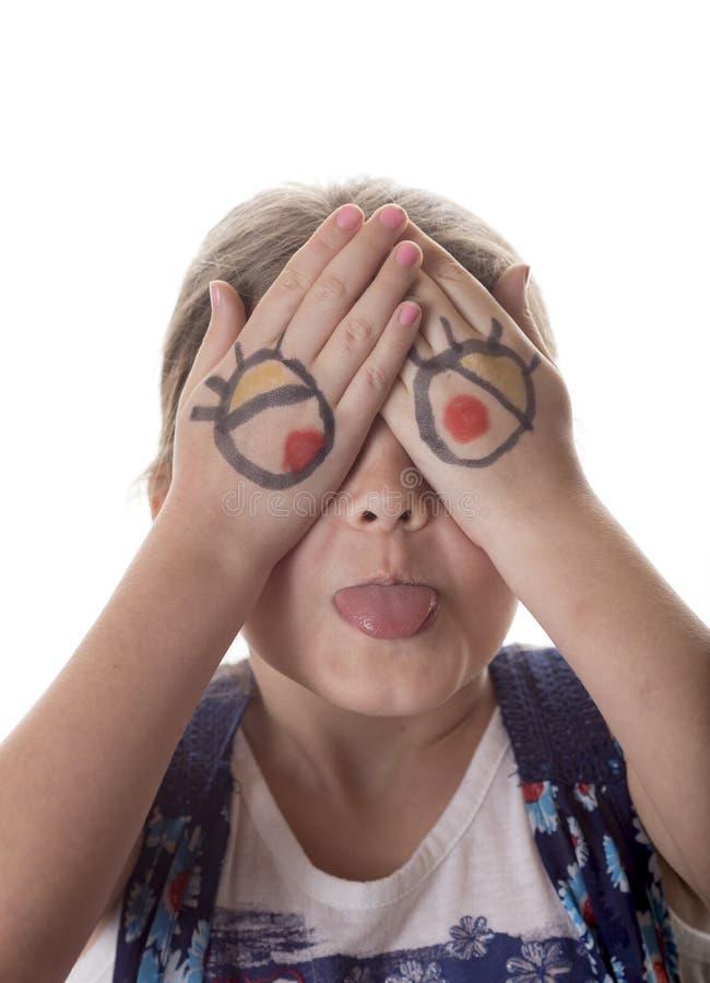 Niña con los ojos de la historieta dibujados en las manos que hacen la cara torpe foto de archivo