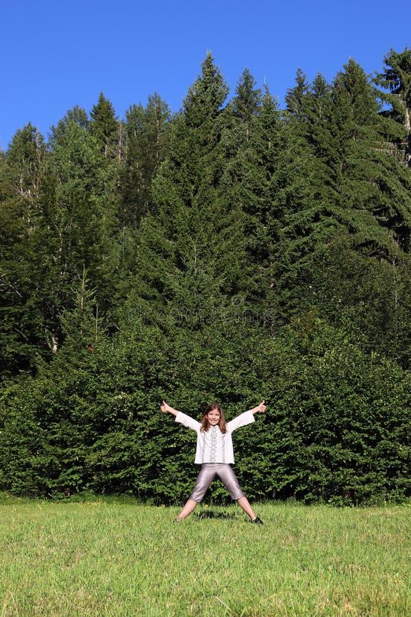 Niña con los pulgares que se levantan delante del bosque foto de archivo