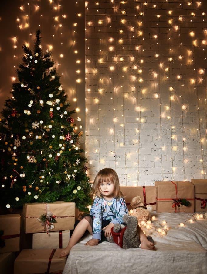 Niña con los regalos de la Navidad cerca del árbol de navidad imagenes de archivo