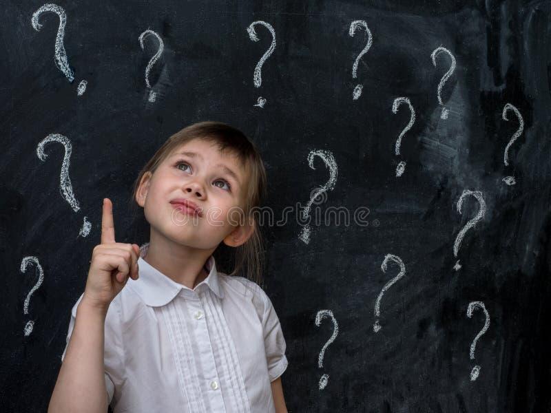 Niña con los signos de interrogación en la pizarra Concepto para la confusión, la reunión de reflexión y la opción foto de archivo
