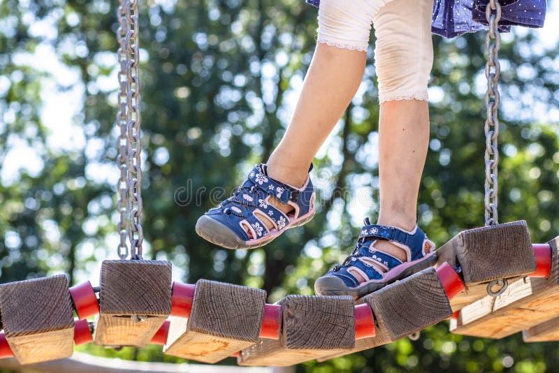 Niña con sandalia que camina sobre el puente imagen de archivo libre de regalías