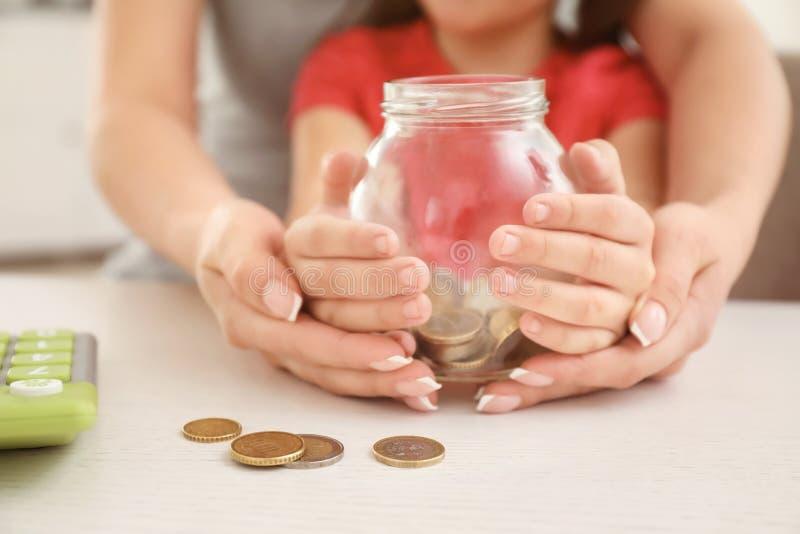 Niña con su madre que se sienta en la tabla y que celebra el tarro de cristal con las monedas, primer Concepto de los ahorros del foto de archivo