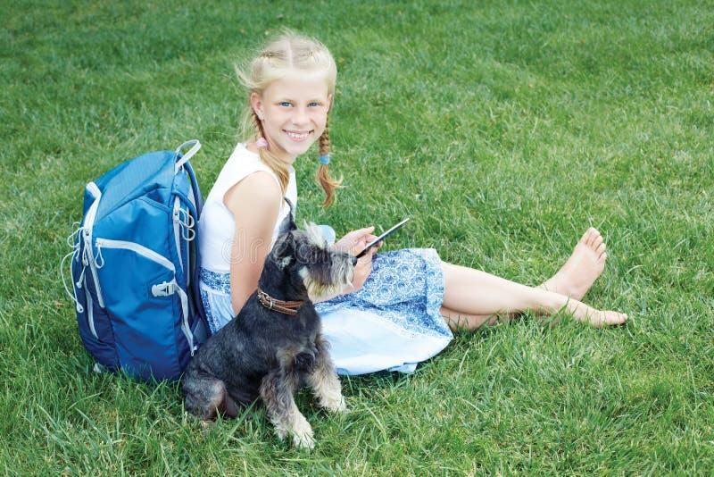 Niña con su perro que se sienta en hierba verde y eBook leído imágenes de archivo libres de regalías