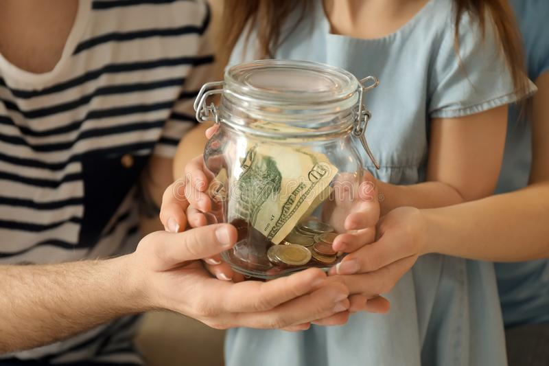 Niña con sus padres que sostienen el tarro de cristal con los dólares, primer Concepto de los ahorros del dinero fotografía de archivo libre de regalías
