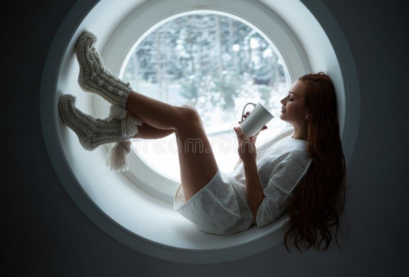 Niña con traje deportivo blanco yace en la ventana imagenes de archivo