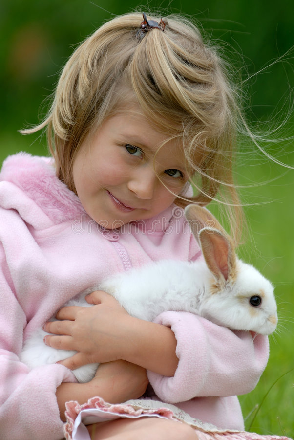 Niña con un conejo imagenes de archivo