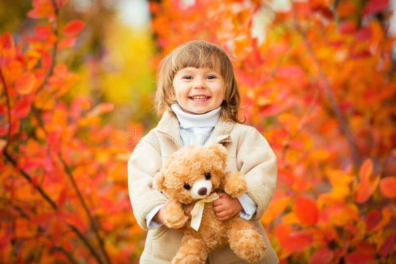 Niña con un oso de peluche en su mano en un fondo del follaje del otoño Autumn Time foto de archivo