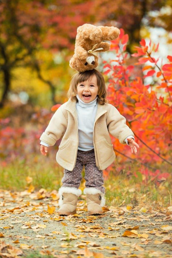 Niña con un oso de peluche en su mano en un fondo del follaje del otoño Autumn Time foto de archivo libre de regalías