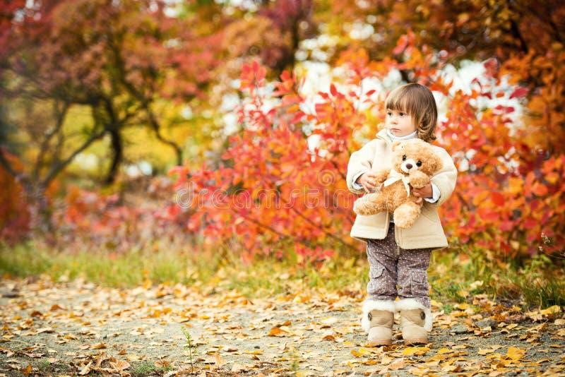 Niña con un oso de peluche en su mano en un fondo del follaje del otoño Autumn Time fotos de archivo libres de regalías