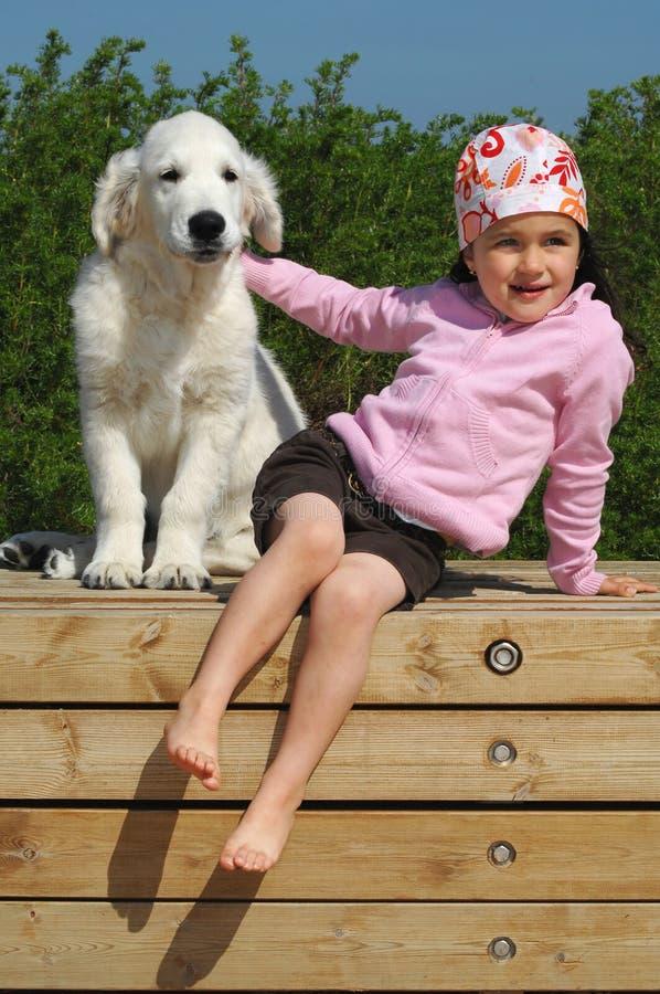 Niña con un perro perdiguero de oro imagen de archivo libre de regalías