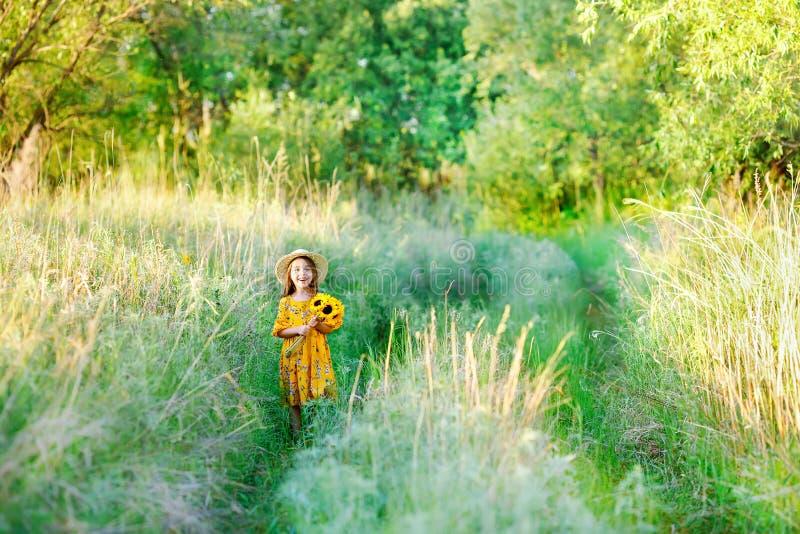 Niña con un ramo de flores amarillas salvajes que se colocan en el día de verano soleado del prado en un sombrero de paja Copie e imágenes de archivo libres de regalías