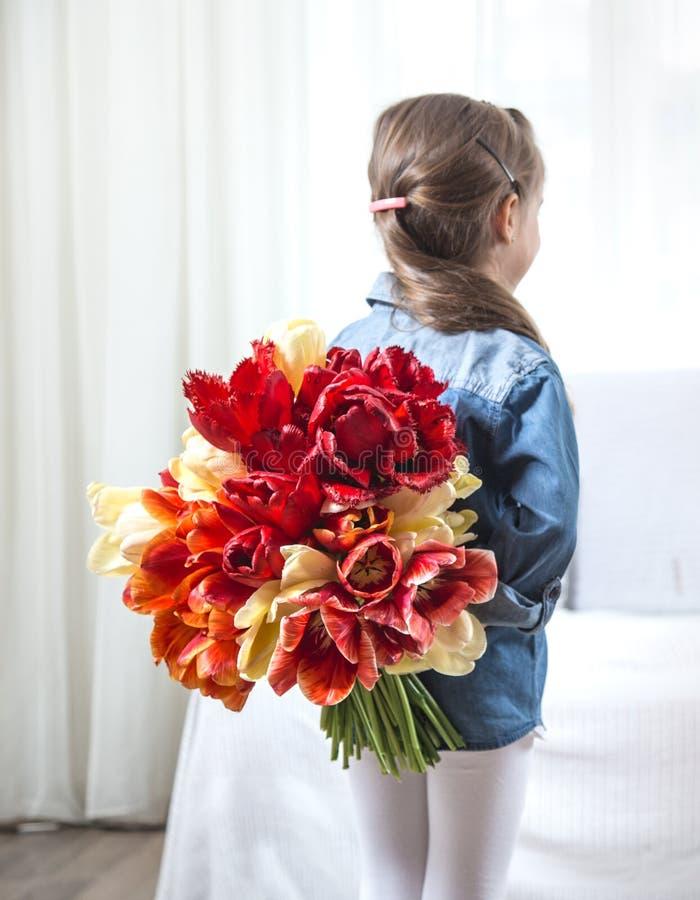 Niña con un ramo grande de tulipanes foto de archivo