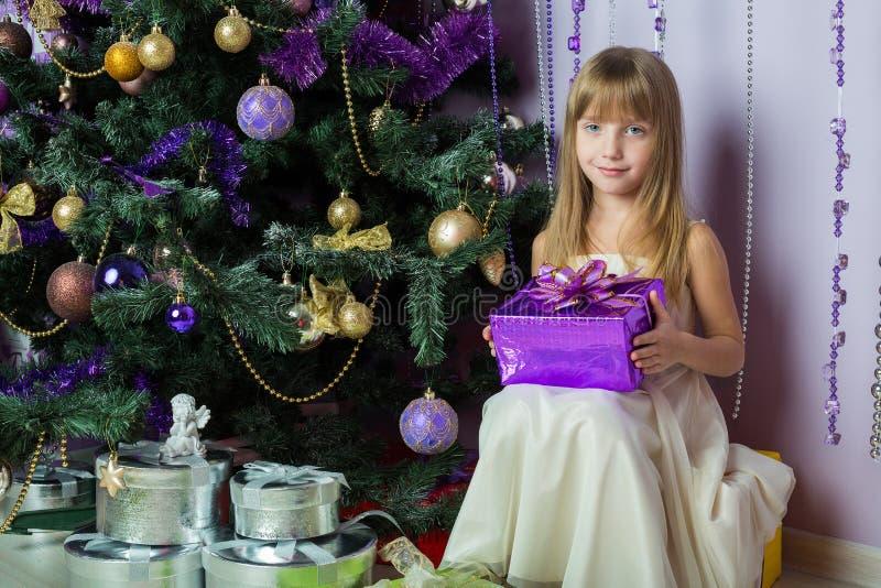 Niña con un regalo que se sienta debajo del árbol de navidad fotografía de archivo