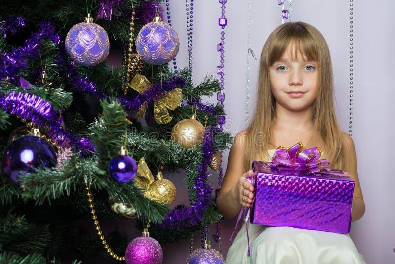 Niña con un regalo que se sienta debajo del árbol de navidad imagen de archivo libre de regalías